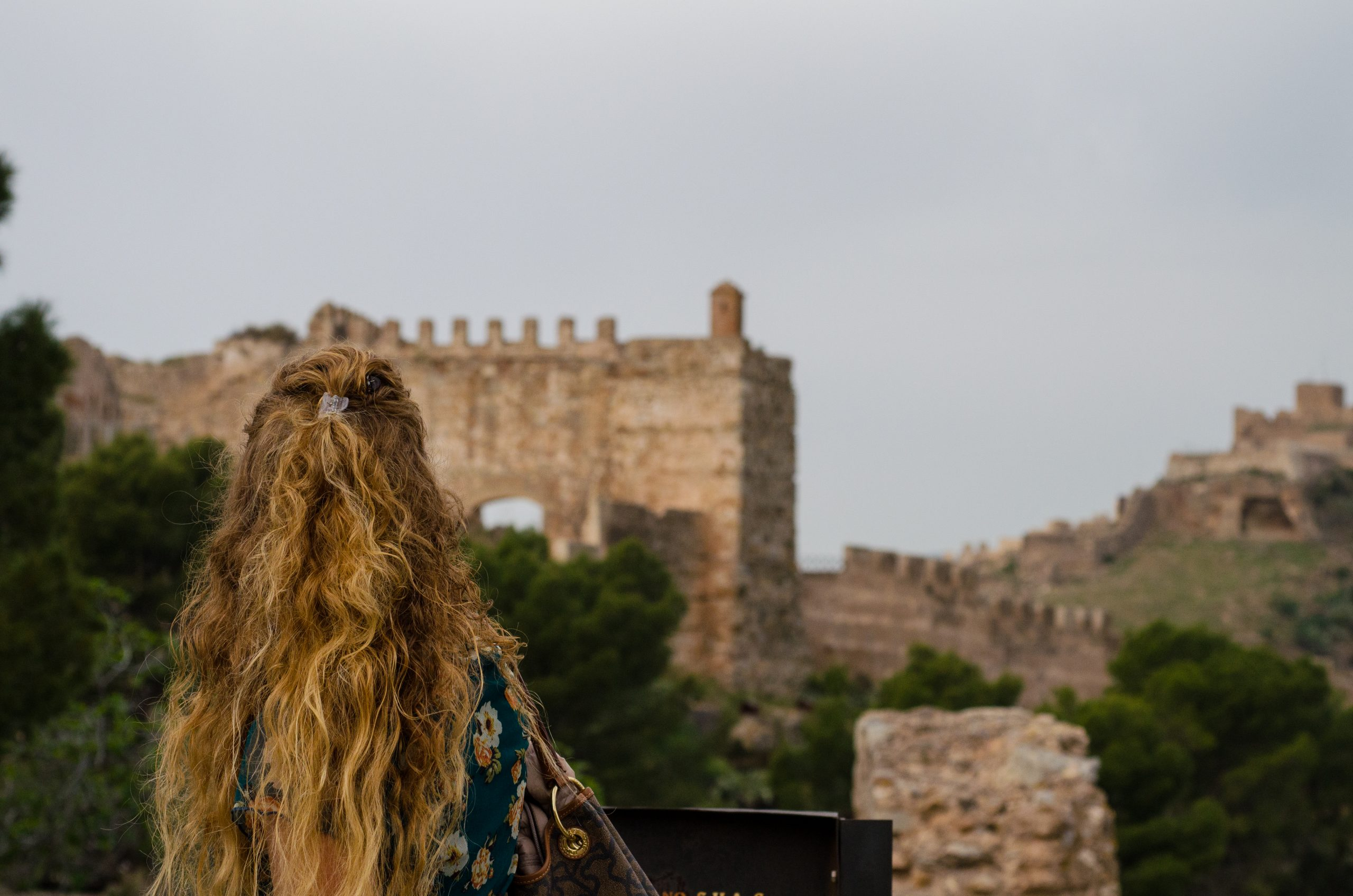 tourist looking at sagunto's ancient ruins